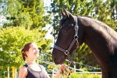 Proche équestre de jeune dame son cheval foncé au hippodrom Photos stock