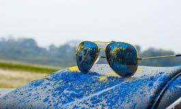 Prochowy błękit i żółty kolor na słońca szkle podczas holi festiwalu fotografia royalty free