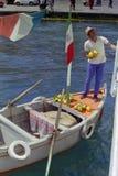 PROCIDA, ΙΤΑΛΙΑ, 1974 - ο λεμβούχος πωλεί τα λεμόνια Procida στους τουρίστες στο πορθμείο που δένεται στο λιμένα άμεσα με τη βάρκ στοκ φωτογραφίες