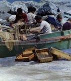 PROCIDA, ITALIA, 1979 - alcuni pescatori riparano le loro reti con abilità e pazienza ed asciugano alcune scatole di pesce nel so immagini stock
