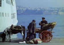 PROCIDA ITALIEN, 1974 - italiensk brevbärare med vagnen och hästen med post- säckar på pir av Procida royaltyfria bilder