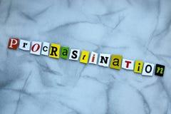 Procrastina??o da palavra de letras cortadas no fundo cinzento Conceito Psychologic T?tulo - procrastina??o Uma palavra que escre imagens de stock