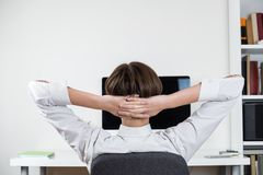 Procrastination concept: office worker stretching in front of black computer screen. royalty free stock images