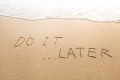 Procrastination or laziness concept, do it later. Text sign on the beach royalty free stock image