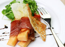 Procuitto ham rolled around fresh melon Stock Images