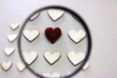 Procurando o coração diferente entre o grupo de madeira os mesmos corações Fotografia de Stock
