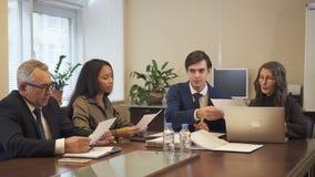 Procuratore legale maschio che dà il progetto del contratto per maturare uomo d'affari e donna di affari afroamericana video d archivio