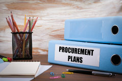 Procurement Plans, Office Binder on Wooden Desk. On the table co. Lored pencils, pen, notebook paper Royalty Free Stock Photo