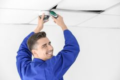 Technician installing CCTV camera on ceiling indoors. Prodessional male technician installing CCTV camera on ceiling indoors Royalty Free Stock Images