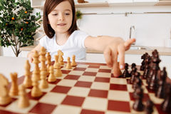 Prodigy girl moving a white pawn. Best game. Cute smart girl reaching out her hand for moving a white pawn while playing along at the chessboard Royalty Free Stock Images