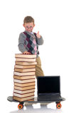 Prodigy internet library surfing. Handsome young child, prodigy, high speed surfing to internet library, metaphor with skateboard, studio shot Royalty Free Stock Image