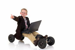 Prodigy internet surfing. Handsome young child, prodigy, high speed surfing on internet, metaphor with skateboard, studio shot Royalty Free Stock Image