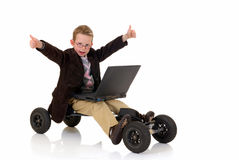 Prodigy internet surfing. Handsome young child, prodigy, high speed surfing on internet, metaphor with skateboard, studio shot Royalty Free Stock Photos