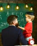 Prodigy-kindconcept Jongen, kind die in gediplomeerd GLB gekrabbel op bord bespreken terwijl leraar het luisteren leraar royalty-vrije stock foto