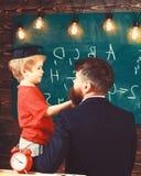 Prodigy-kindconcept Jongen, kind die in gediplomeerd GLB gekrabbel op bord bespreken terwijl leraar het luisteren leraar royalty-vrije stock fotografie