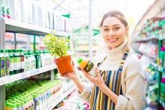 Prodotti agrochimici d'acquisto del giardiniere felice della donna per le piante Fotografia Stock