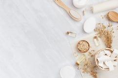 Prodotti bianchi dei cosmetici della stazione termale rustica naturale tradizionale ed accessori beige del bagno su fondo di legn immagine stock