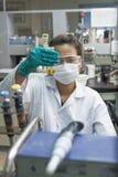 Prodotti chimici d'esperimento di signora in vetri della prova Fotografia Stock Libera da Diritti