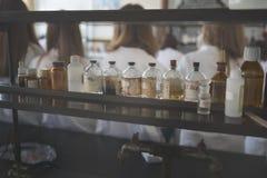 Prodotti chimici ed utensili del laboratorio bottiglie d'annata della farmacia sul bordo di legno Bottiglie chimiche per uso sull Fotografia Stock Libera da Diritti