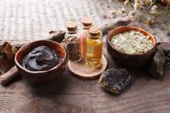 Prodotti di cura di pelle di erbe naturali, ingredienti di vista superiore Olio cosmetico, argilla, sale marino, erbe, foglie del fotografie stock