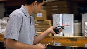 Prodotti di esame del lavoratore con un lettore di codici a barre stock footage