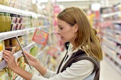 Prodotti di esame della venditora con la compressa immagine stock libera da diritti