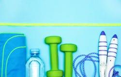 Prodotti di forma fisica, teste di legno, scarpe da tennis, bottiglia di acqua, corda di salto, asciugamano, vista superiore, con fotografia stock