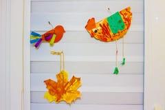 Prodotti fatti di carta sulla finestra Creatività del bambino sulla finestra Uccelli di carta e una foglia su una finestra bianca Fotografia Stock Libera da Diritti