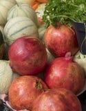 Prodotti freschi con i melograni, rockmelons, prezzemolo fotografie stock
