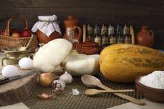 Prodotti freschi per una dieta sana: zucca, zucca, mele, due uova del pollo, farina di frumento, cipolle, aglio, brocche con latt Immagini Stock Libere da Diritti