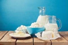 Prodotti lattier-caseario sulla tavola di legno sopra fondo blu Fotografie Stock Libere da Diritti
