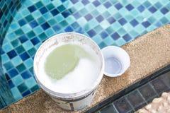 Prodotto chimico in recipiente di plastica sul bordo della piscina, trattamento delle acque per la piscina Fotografie Stock Libere da Diritti