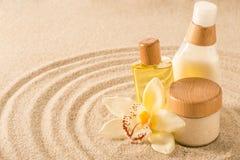 Prodotto del corpo della stazione termale sul fiore dell'orchidea della sabbia Fotografia Stock Libera da Diritti