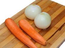 Prodotto-verdure fresche di vegetables Carote e cipolle su un bordo di legno per tagliare Fotografia Stock
