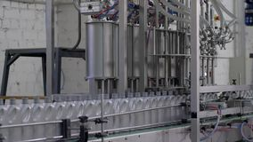 Produção de óleo de motor, fileira de garrafas plásticas cinzentas em linha movente do transporte na fábrica filme