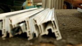 A produção de janelas do pvc, o trabalhador masculino punciona os detalhes de uma janela do perfil do pvc, close-up, equipamento filme