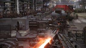 Produção perigosa do metal O plano geral das máquinas em que move o aço quente vídeos de arquivo