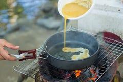 Produca un'omelette sulla pentola in olio caldo, disponga sulla stufa, prepari la prima colazione per l'escursione o il campeggio Immagine Stock
