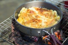 Produca un'omelette sulla pentola in olio caldo, disponga sulla stufa, prepari la prima colazione per l'escursione o il campeggio Immagini Stock