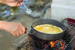 Produca un'omelette sulla pentola in olio caldo, disponga sulla stufa, prepari la prima colazione per l'escursione o il campeggio Immagine Stock Libera da Diritti