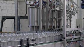 Producción de aceite de motor, fila de botellas plásticas grises en línea móvil del transportador en fábrica metrajes