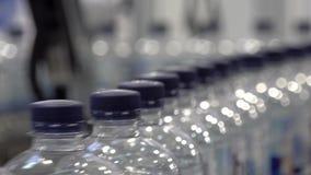 Producción de agua potable en las botellas plásticas que mueven encendido la banda transportadora almacen de metraje de vídeo