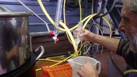 Producción de esencias del perfume por la destilación de vapor en cubo de la destilación en un pequeño pueblo alpino almacen de metraje de vídeo