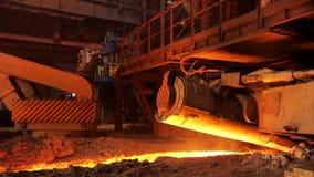 Producción de fundición en la fábrica, concepto de la metalurgia Cantidad común Acero fundido que fluye en canal inclinado metalú almacen de video