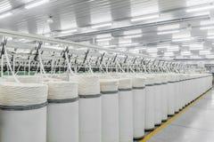 Producción de hilos en una fábrica de la materia textil foto de archivo