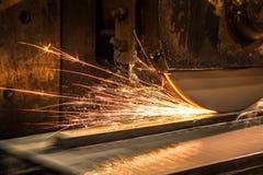 Producción de partes en la industria metalúrgica, acabando en la máquina de pulir con las chispas del vuelo foto de archivo libre de regalías