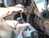 Producción de partes en un torno del metal Un trabajador comprueba el tamaño w Foto de archivo libre de regalías