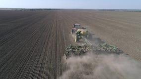 Producción vegetal, sembrando la máquina con el grano de semilla de la paleta en el suelo del campo en el establecimiento de la e metrajes