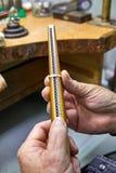 Producci?n de la joyer?a El joyero hace un anillo de oro El proceso de medir el anillo foto de archivo