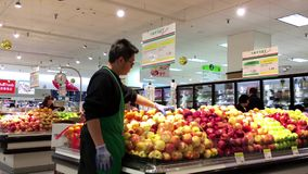 Produce clerk stocking fruit for sale stock video footage